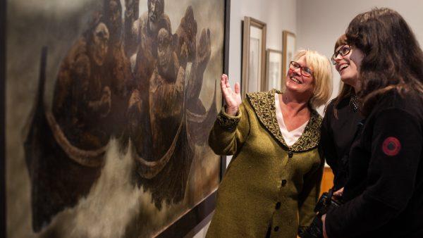 Tre damer ser på kunst